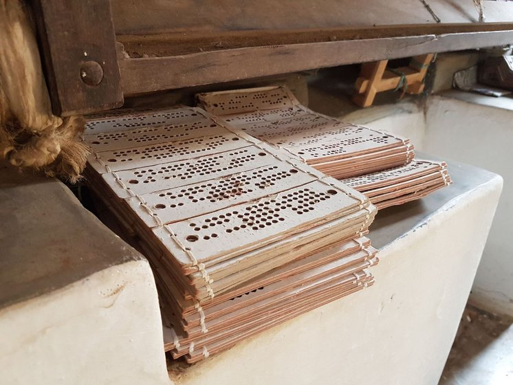 Stacks of punched cards to be used in the jacquard machine, kept in a corner. Shot inside Mani's house.