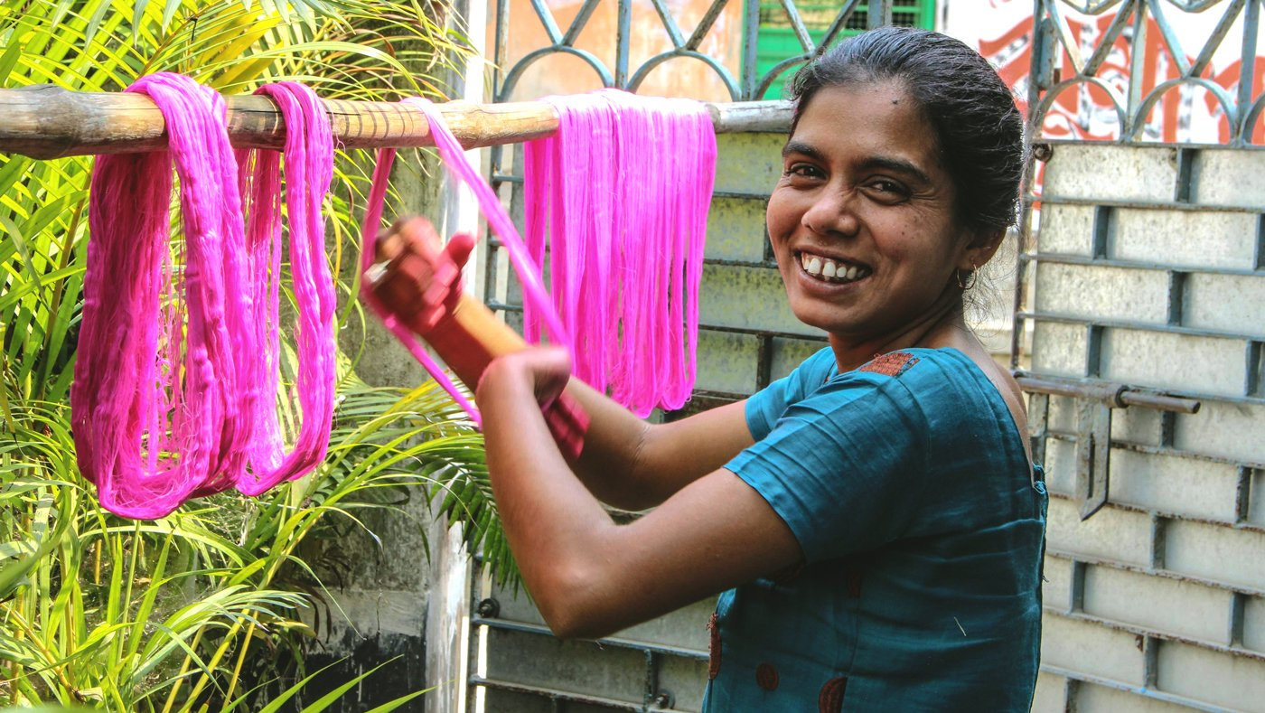 Woman drying coloured yarn