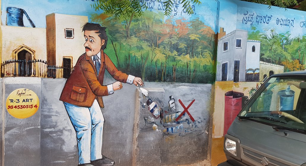 painting on the wall of a man throwing garbage