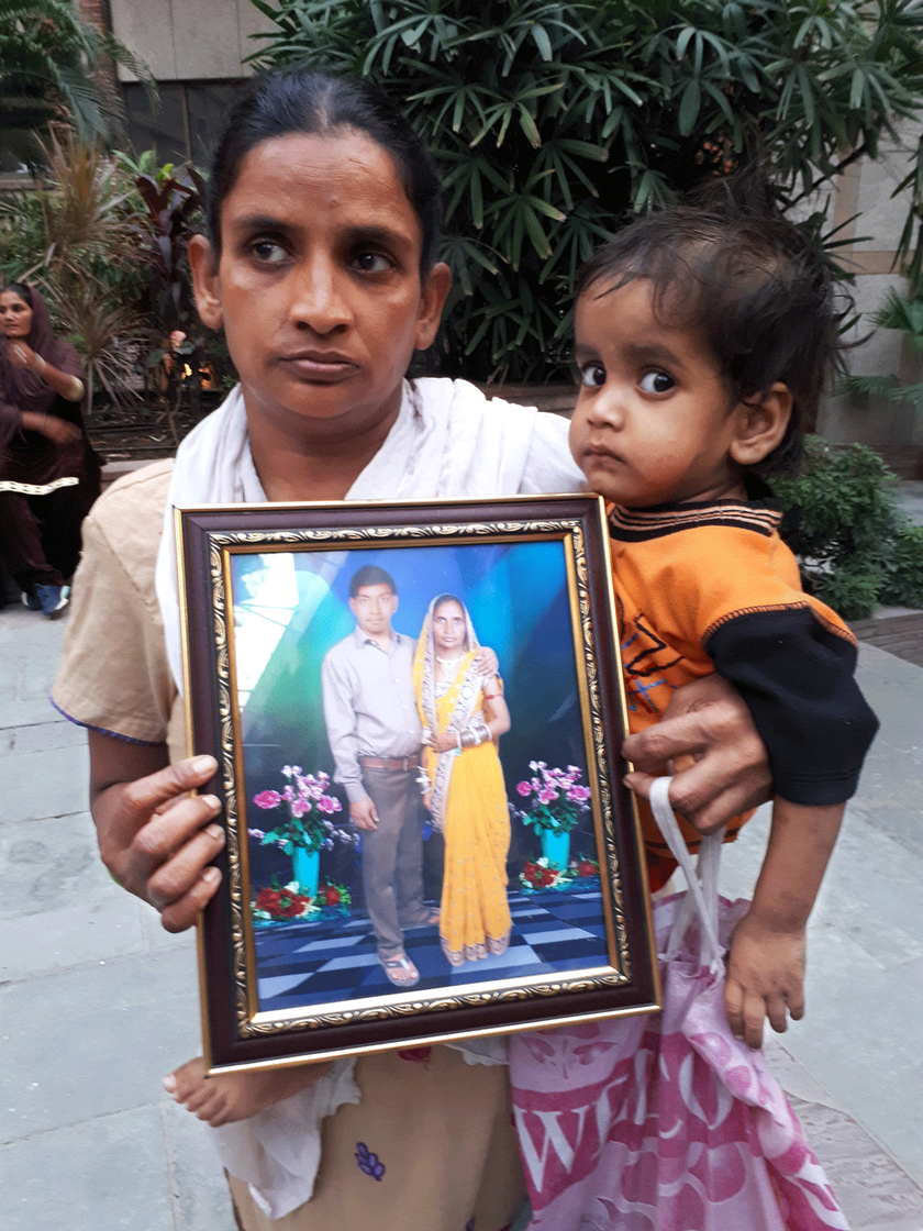 Rani holds her son in one hand and a frame of her and her husband on the other.