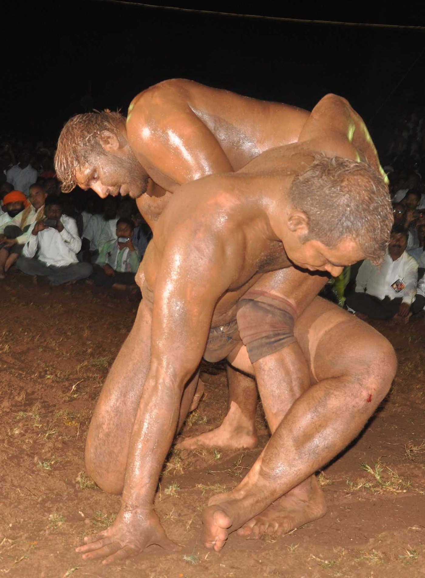 Two men wrestling in mud