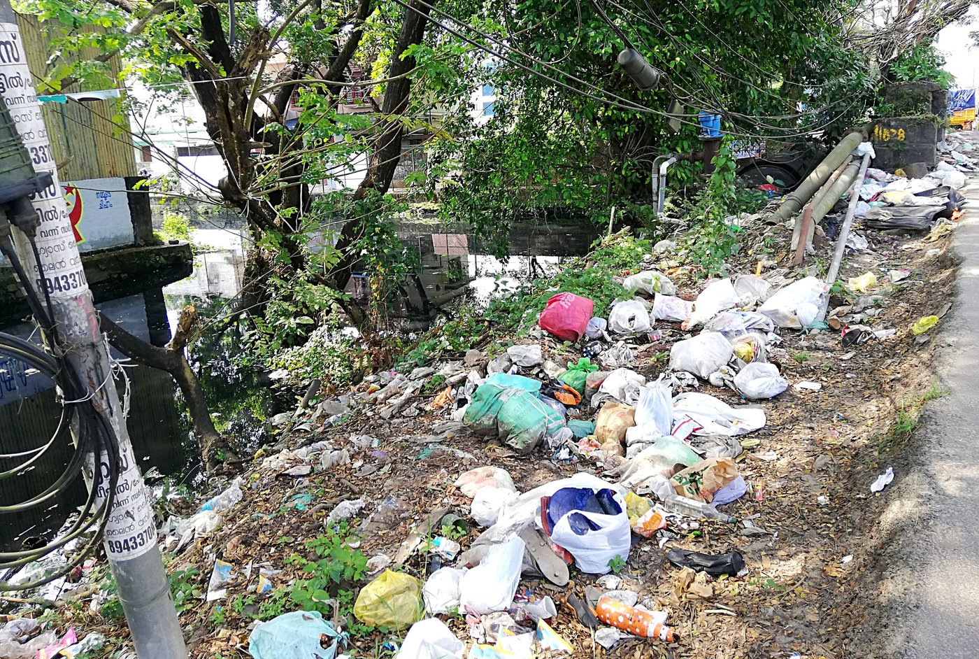 Left: A bridge on the canal that reduces its width and slows down the flow of water. Right: Waste dumped by Kochi city residents on the canal banks