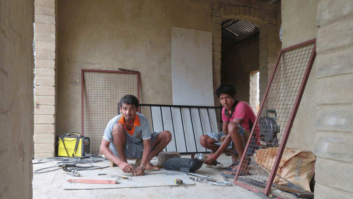 Young men installing window grille