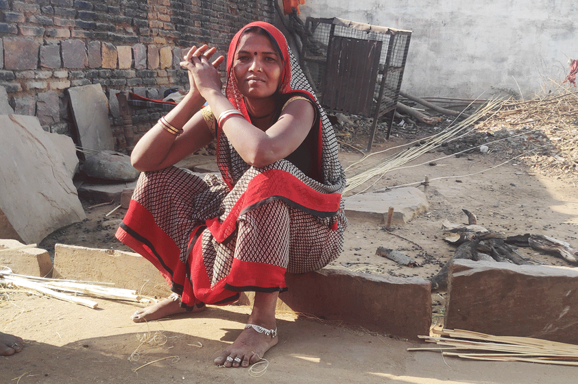 Rajabeti sitting near the broken roads