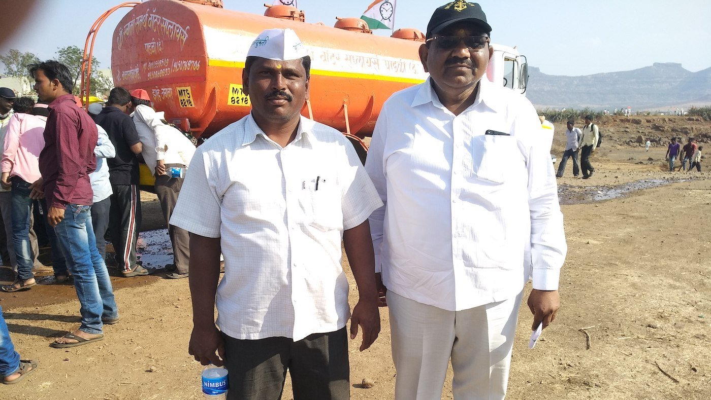 Farmers standing in front of a tanker