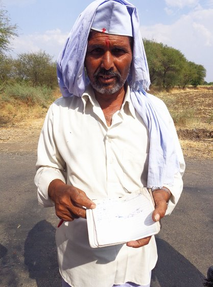 Farmer showing his diary with all loan entries