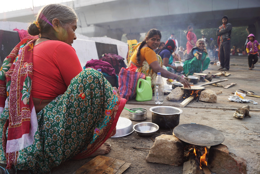 Women cook for their families on the side of the road