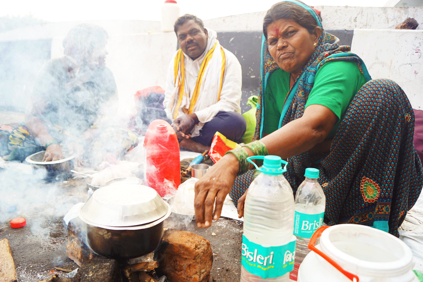 Laxmibai Kharat cooks for her family on the side of the road.