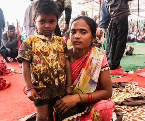 Child with mother sitting under the canopy at Ramleela maidan