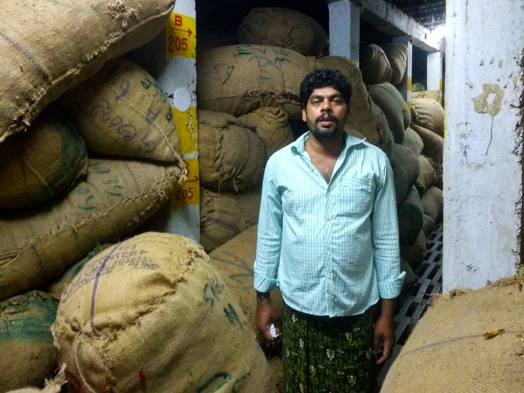 Man standing amid sacks of chillies in cold storage