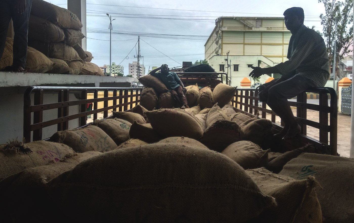 workers seating in a truck of loaded sacks of mirchi