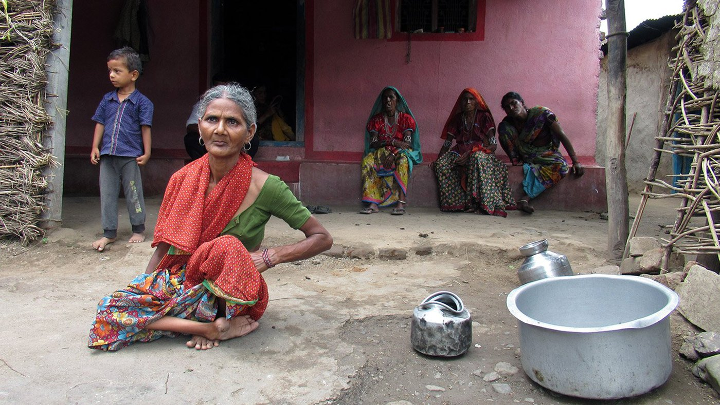 Old woman with her family with empty vessels
