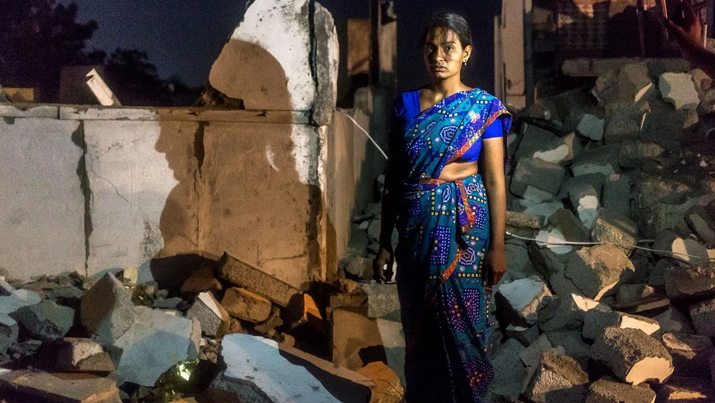 woman standing near ruins of home