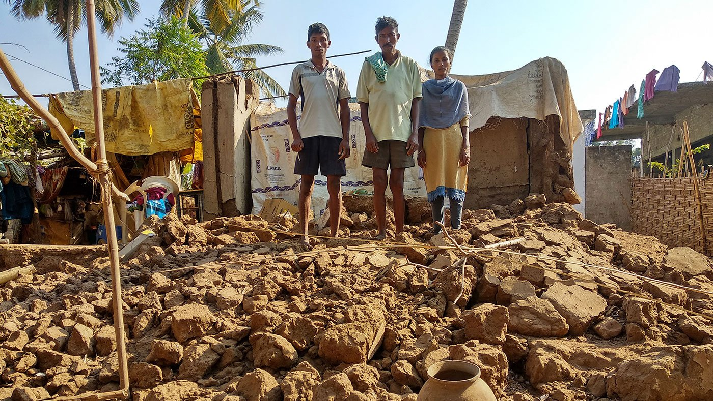 Bapiraju, his son Mutyala Rao and his daughter Prasanna Anjali stand on the top of the ruins of their house which got collapsed during the floods
