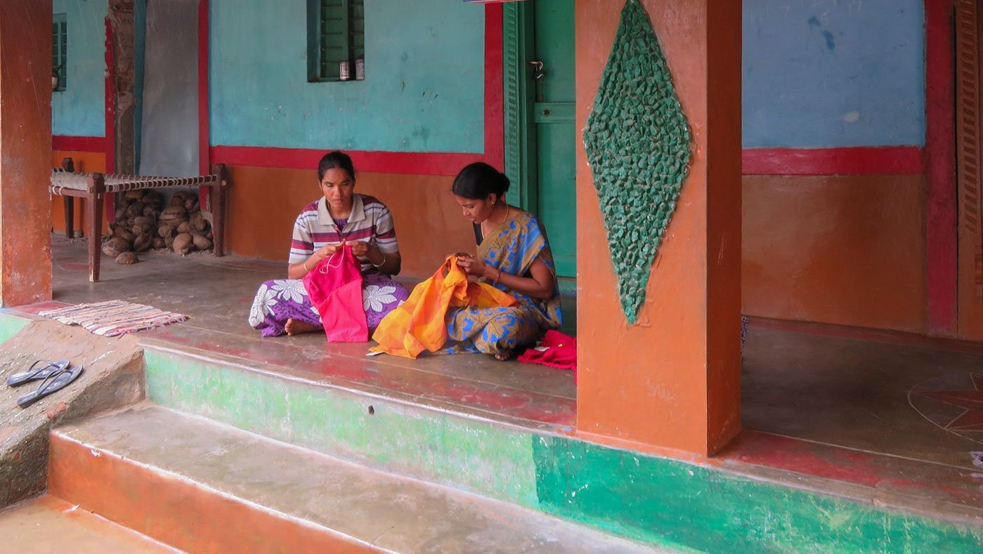 Women sitting in veranda sewing