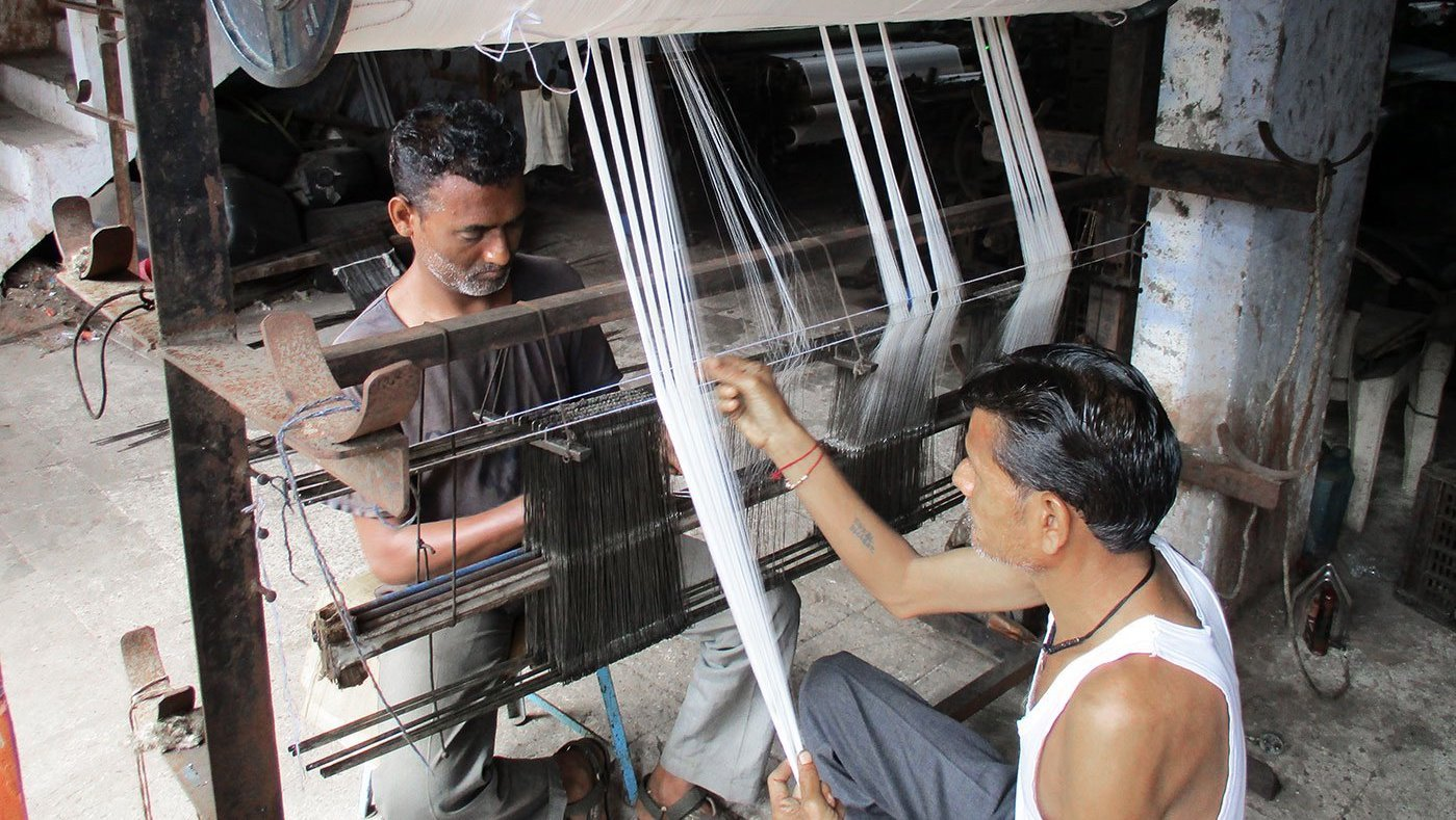 Two men working at a power loom