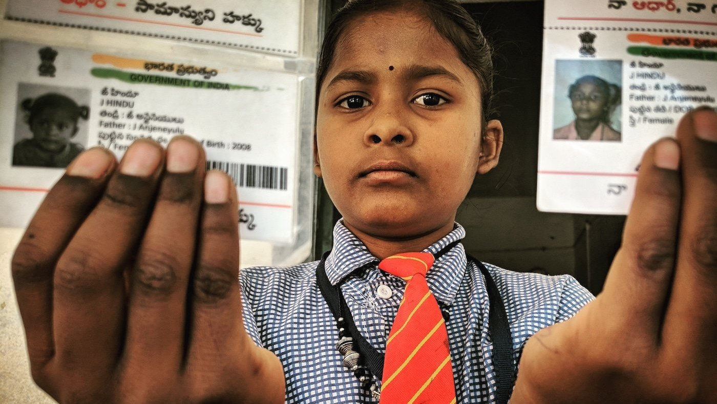 J. Indu holding her Aadhaar cards with her name misspelt