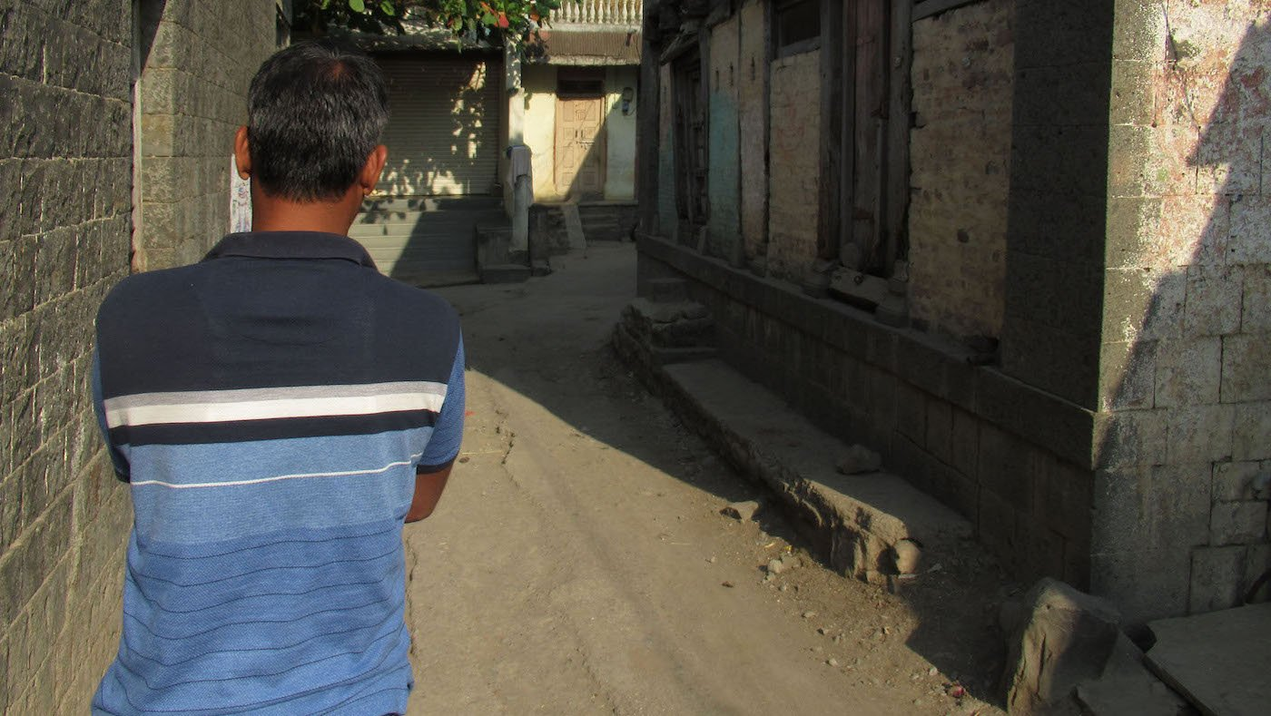 man with back towards camera walking on empty village street
