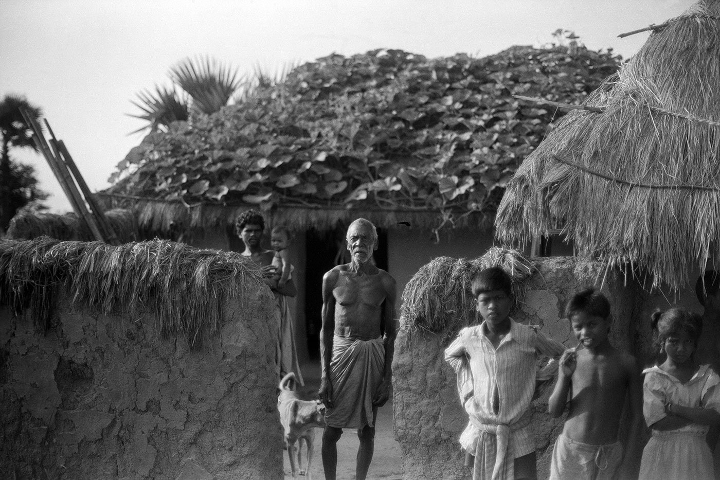 A man standing in front of his hut with three small boys. He has a garden on the roof of his hut.