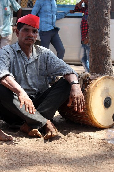 man sitting next to a drum