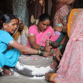 Women sitting by the grinding stone