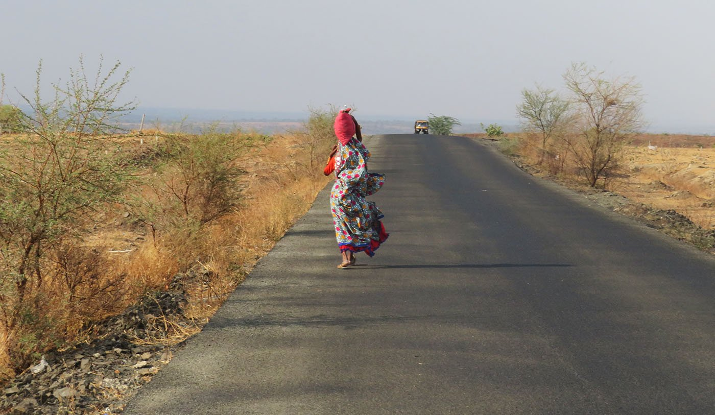 woman walking on road carrying water