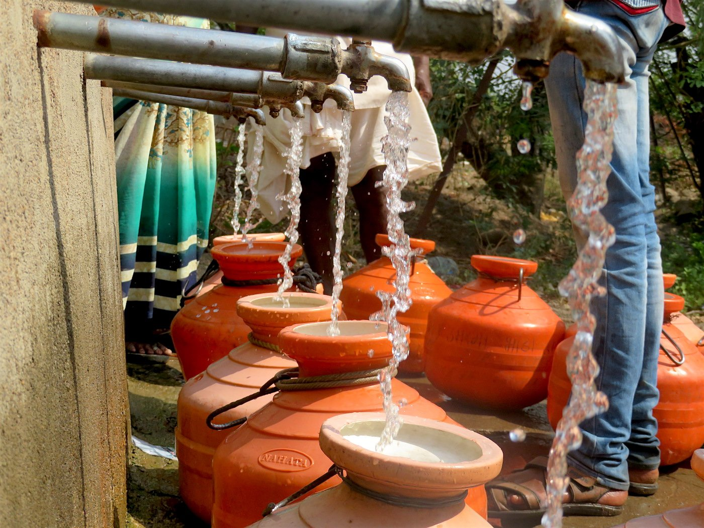 pots are filling with the water from tap