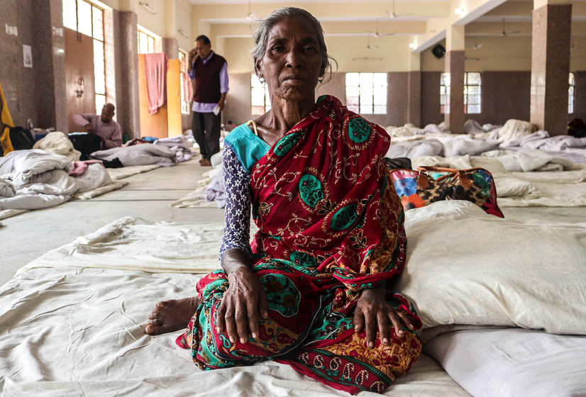 Old woman sitting on makeshift bed