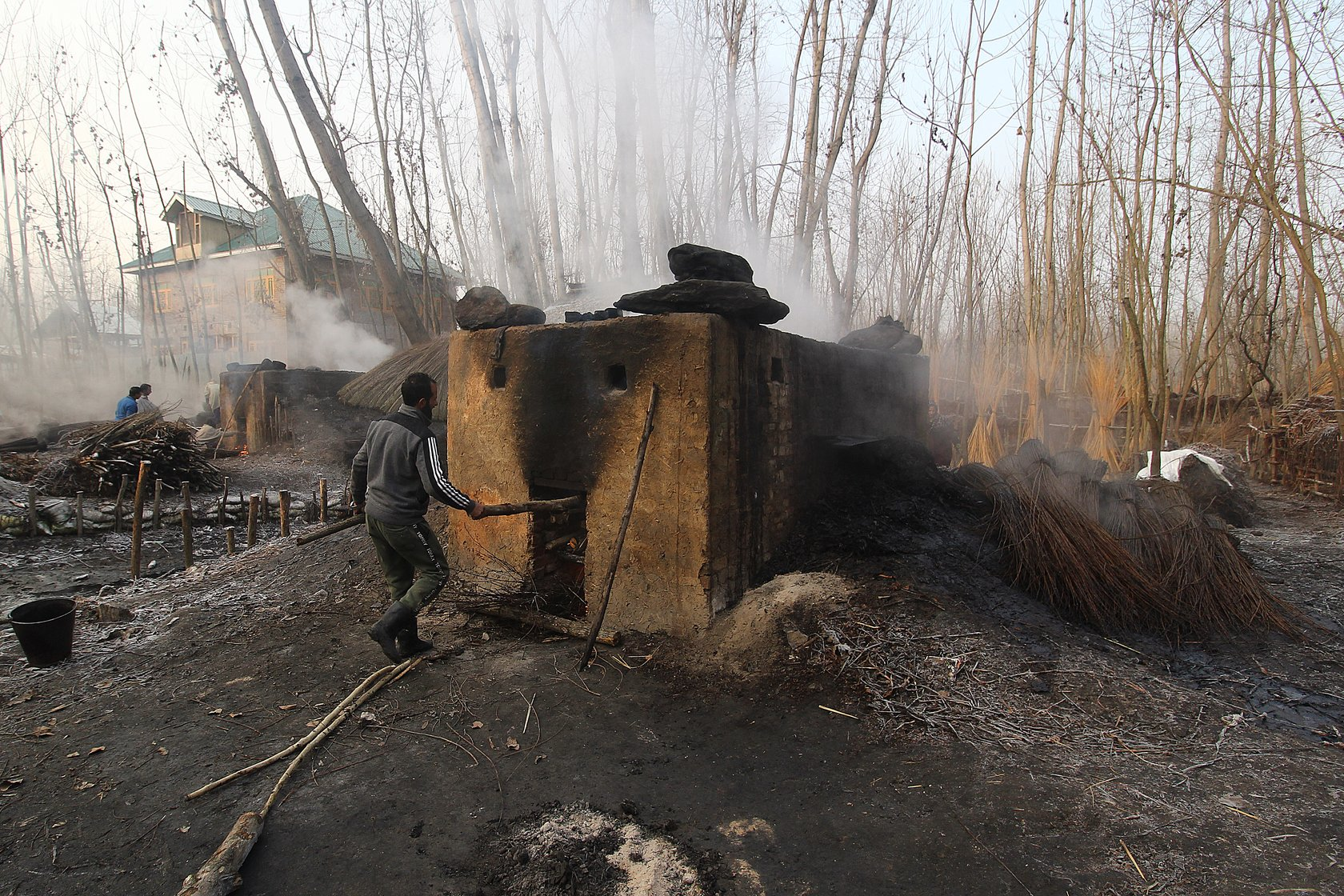 Waseem Ahmad, 32, a resident of Umerhere, fills firewood in the oven in which the wicker is to be boiled overnight