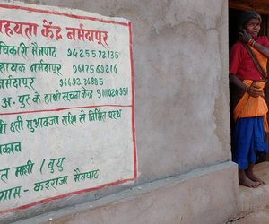 Adivasi woman standing next to wall with warning sign