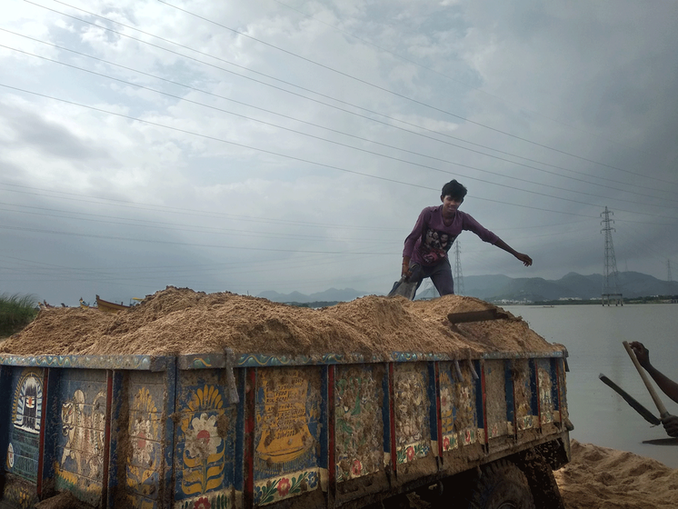 man standing on a truck loaded with sand.