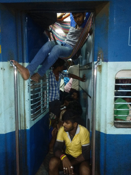 men sitting and hanging in the train.