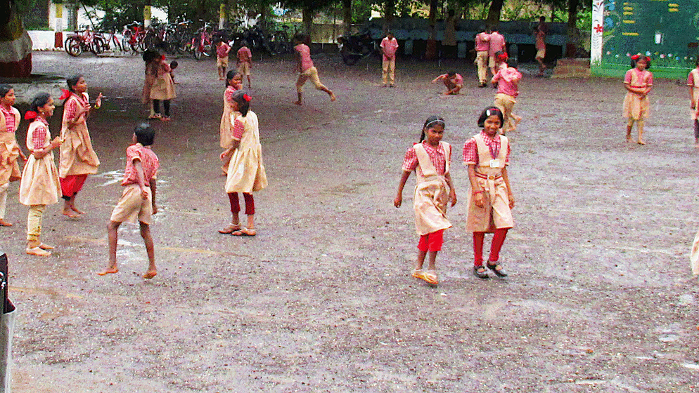 Children playing in school ground; rain
