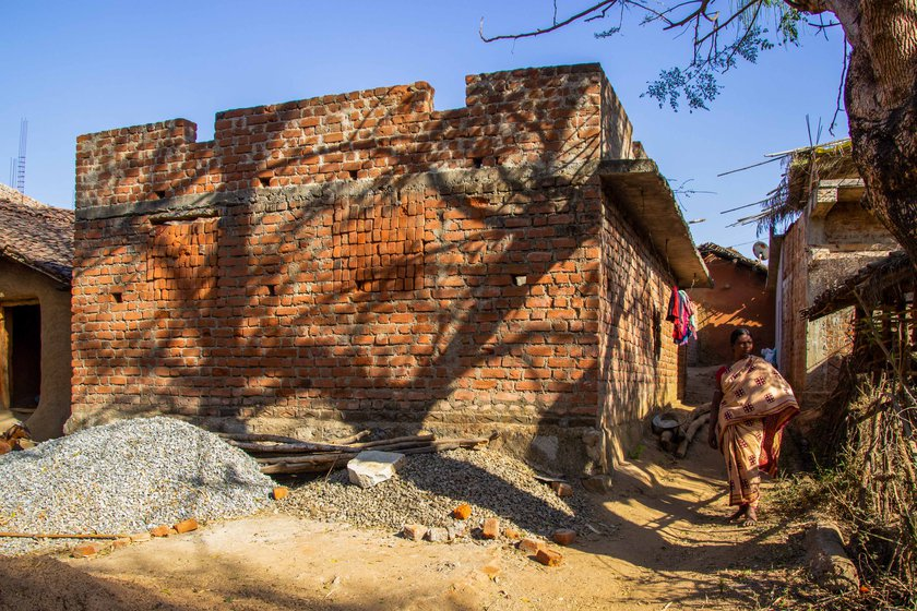 Supari Putel in front of her mud house and the family's incomplete house (right) under the Pradhan Mantri Awaas Yojana: 'This house cost me my husband'