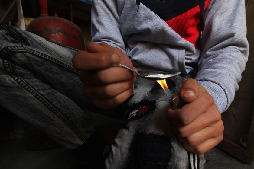 Left: A young boy in a village on the outskirts of Srinagar using heroin.
