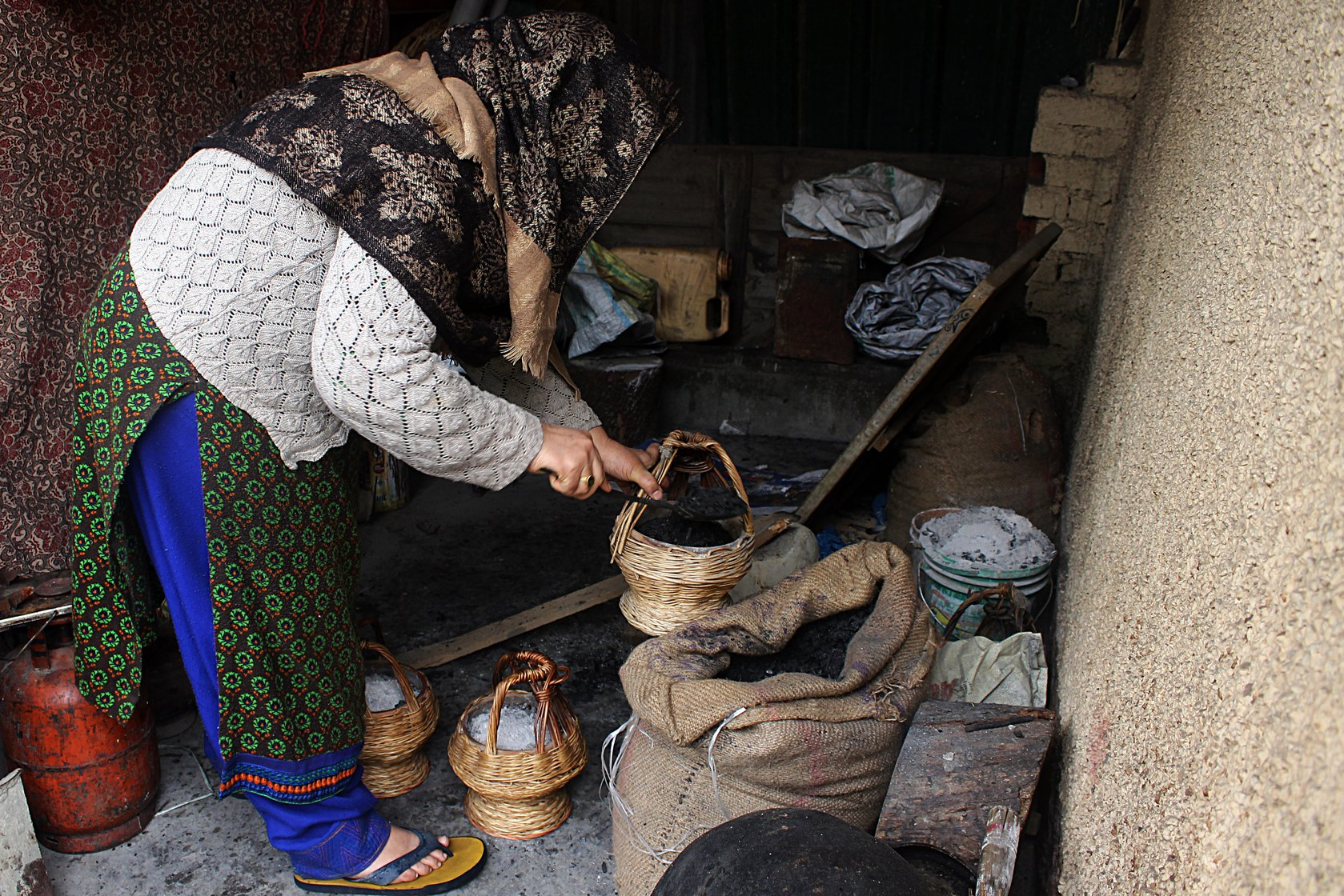 Firdousa Wani, 55, who lives in the Nawakadal area of Srinagar city, filling a kangri with charcoal in a shed (locally called ganjeen) outside her house early one morning