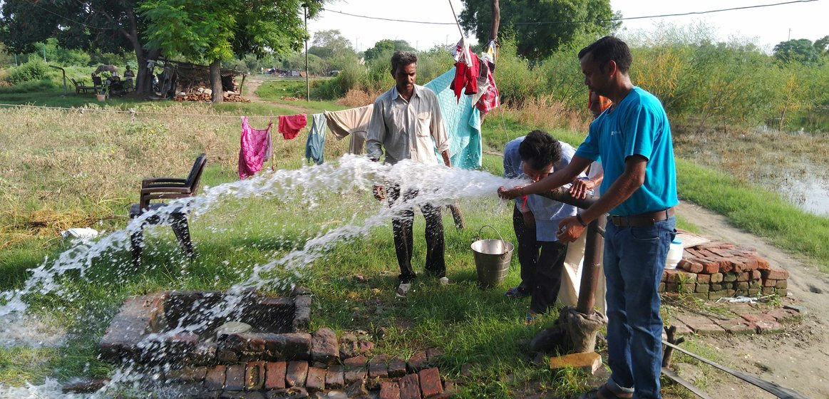 Shiv Shankar and his son Praveen Kumar start the watering process on their field