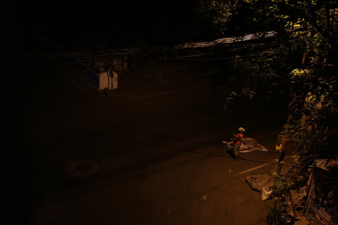 A woman stands alone in the dark after collecting garbage from the streets