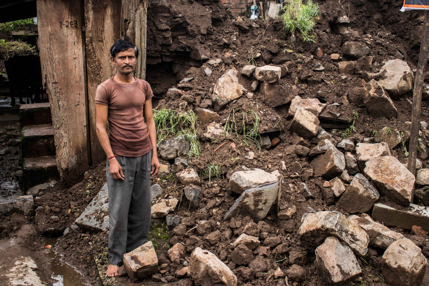 Man stands next to the debris of his flood-ravaged house.