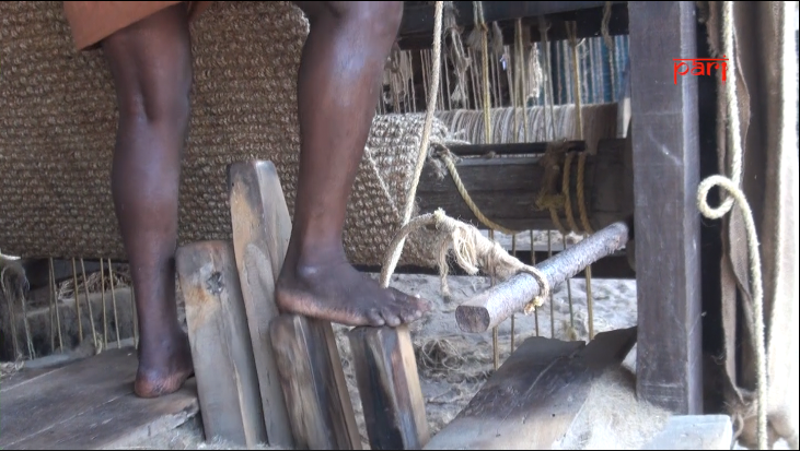 A coir weaver's feet in front of a coir loom
