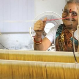 Smiling woman weaving on a handloom