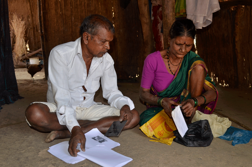 Old couple sitting on ground, looking at documents