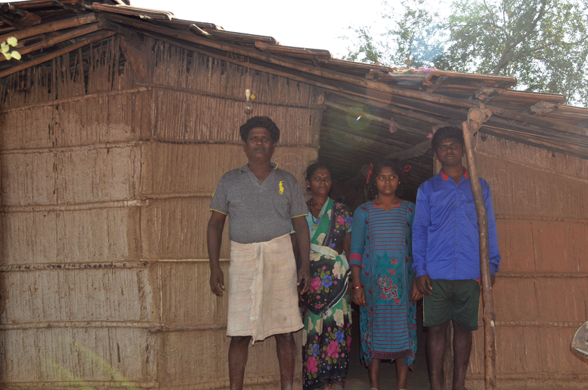 Family standing outside their hut