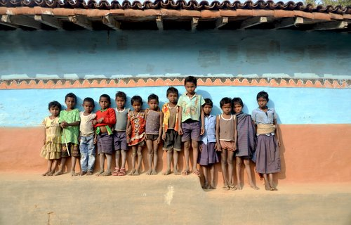 Santhal children standing in front of painted wall