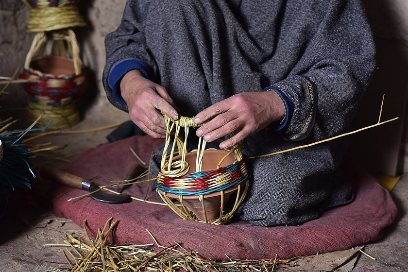 Left: Manzoor Ahmad, 40, weaving a colourful kangri at a workshop in Charar-i-Sharief in Badgam district. Right: Khazir Mohammad Malik, 86, weaving a monochromatic kangri in his workshop at Kanil mohalla in Charar-i-Sharief