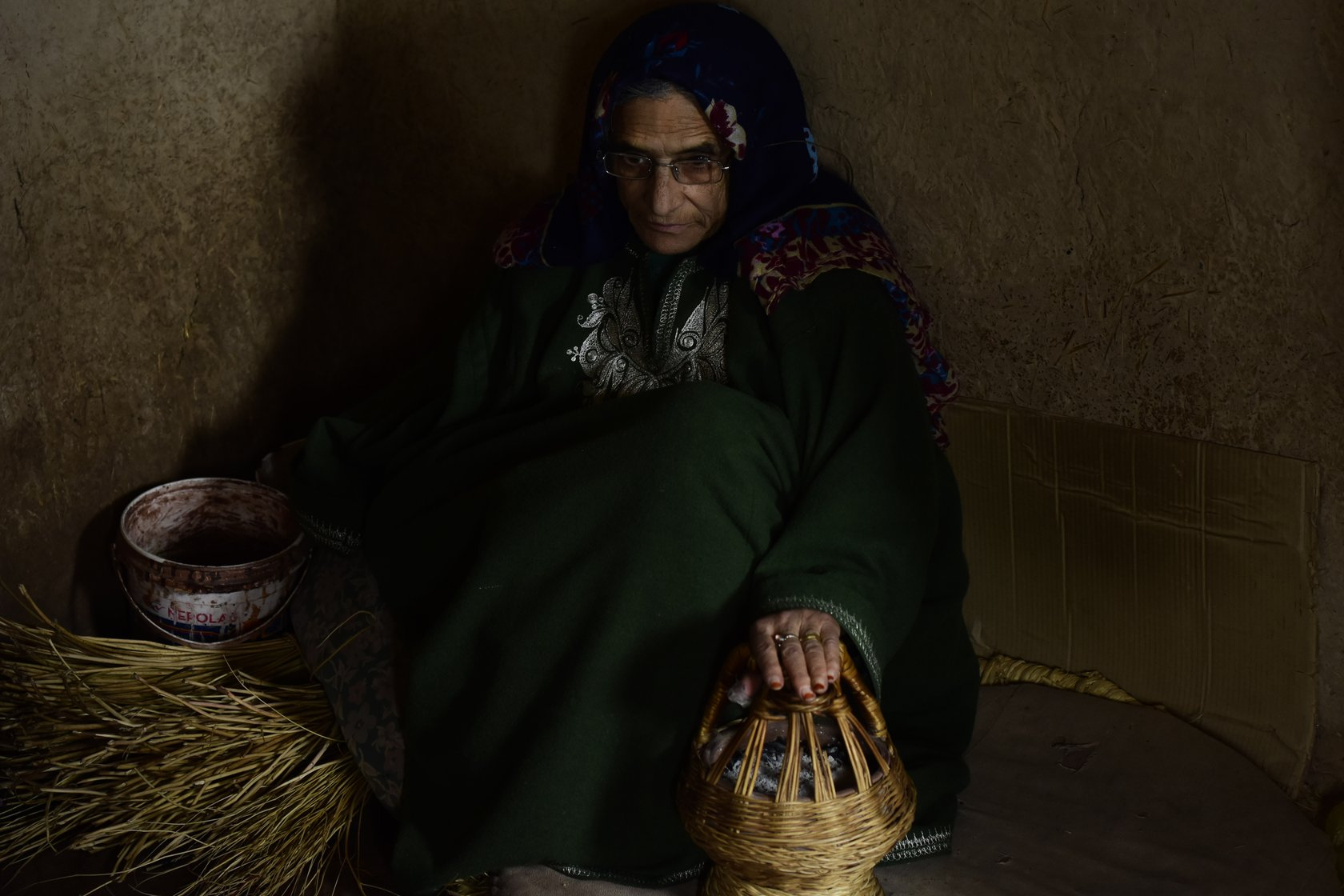 "Mugli Begum, a 70-year-old homemaker in Charar-i-Sharief, says, ""I have seen my husband [Khazir Mohammad Malik] weaving kangris for 50 years and I am happy with his work. Watching him weave a kangri is as good as weaving a kangri'"