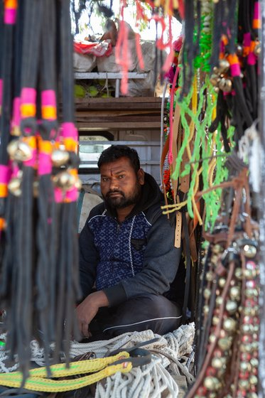 Shopkeeper sitting in his shop, selling accessorizes of livestock.