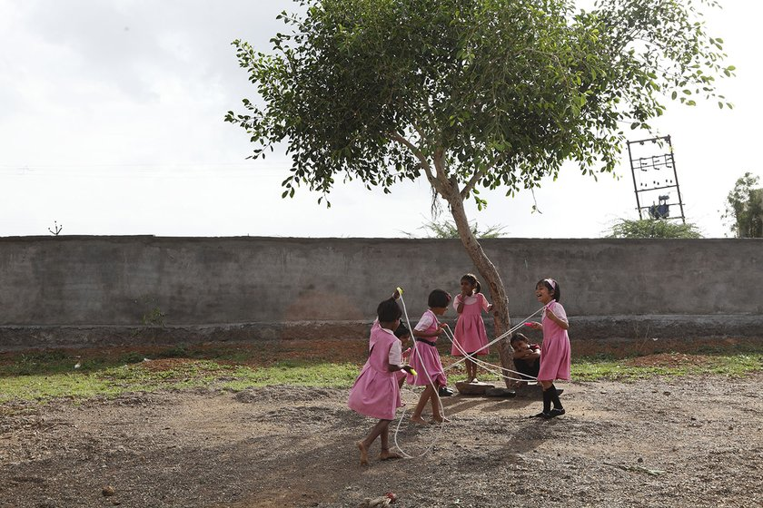 Girls skipping under the tree on their school playground
