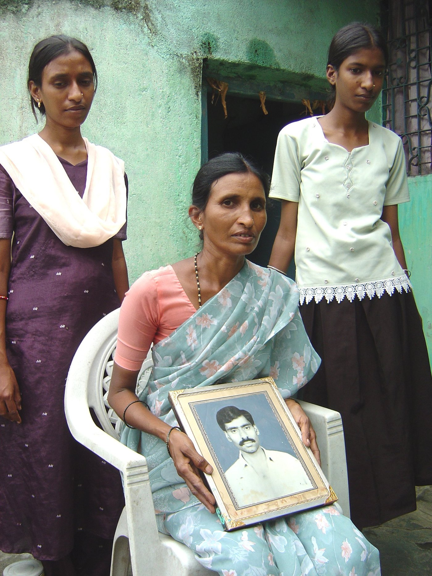 Saraswati Amberwar sitting with a photo of her deceased husband