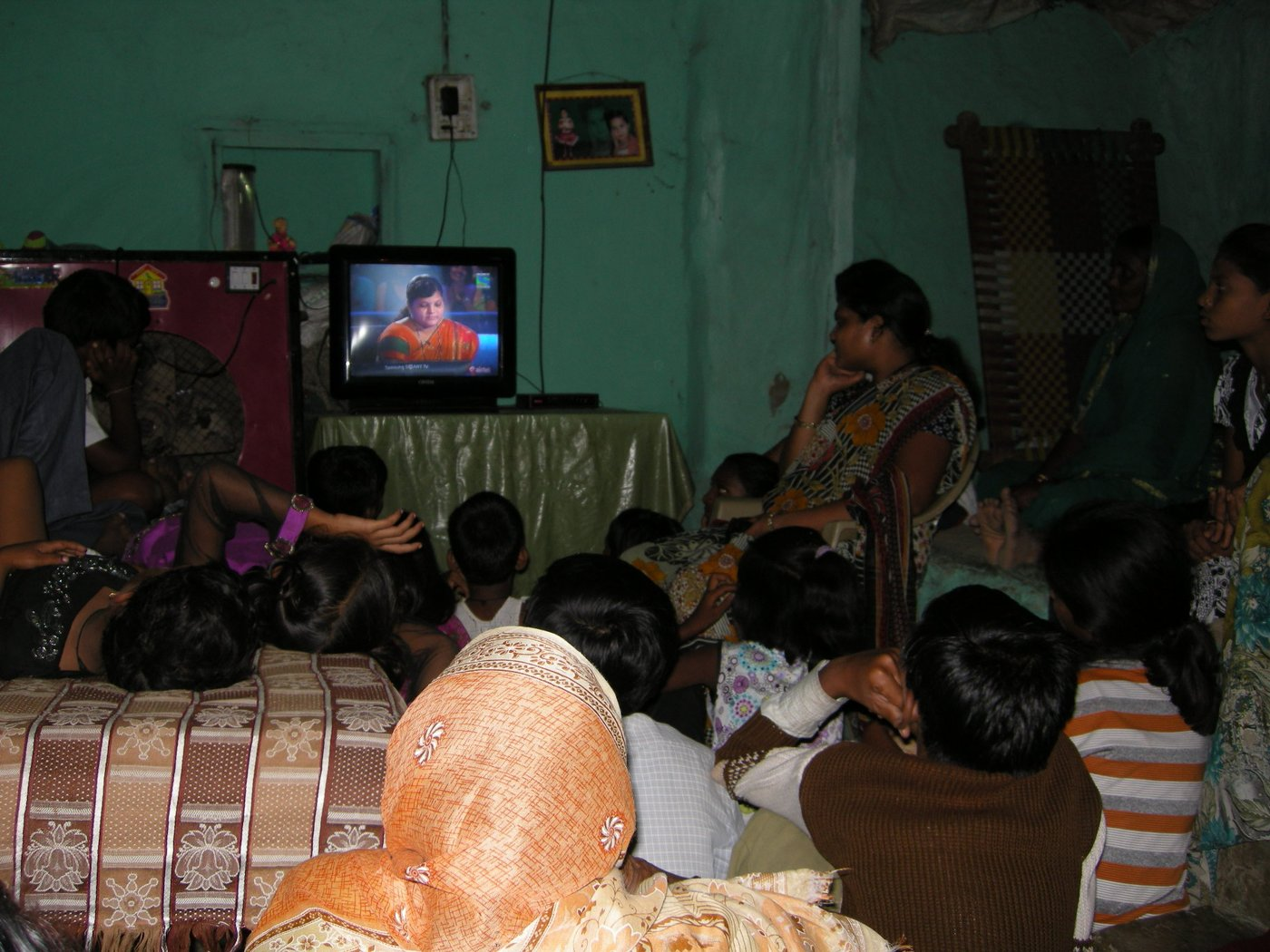 A group of people watching Kaun Banega Crorepati on television